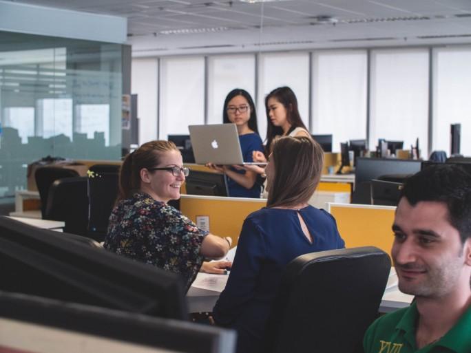 外資系オフィス内の様子。様々な国籍の男女が綺麗なオフィスで仕事をしたり打ち合わせをしている。