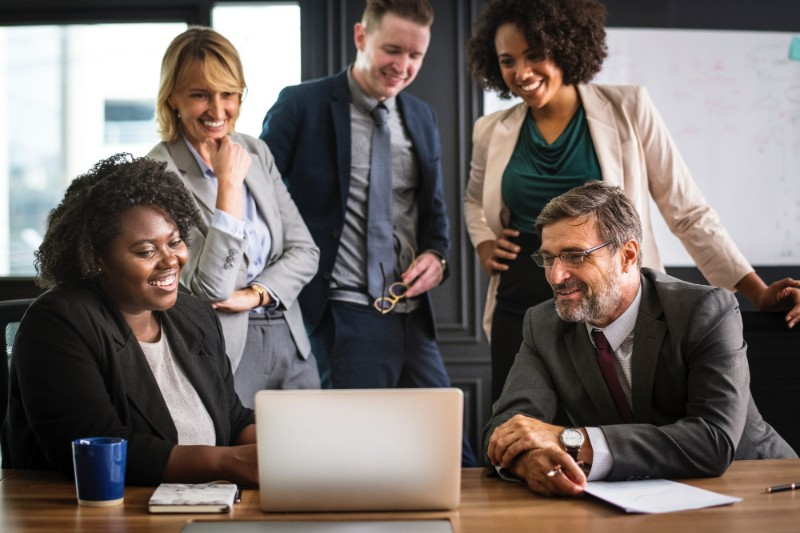 外資系オフィス。様々な国籍の男女が1つのパソコンを見ながら、打ち合わせをしている。